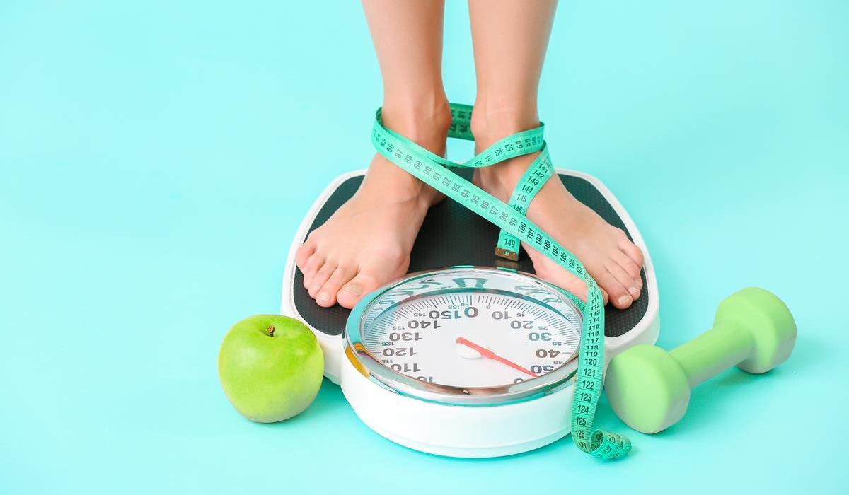 osoba sprawdzająca swoją wagę po zastosowaniu diety